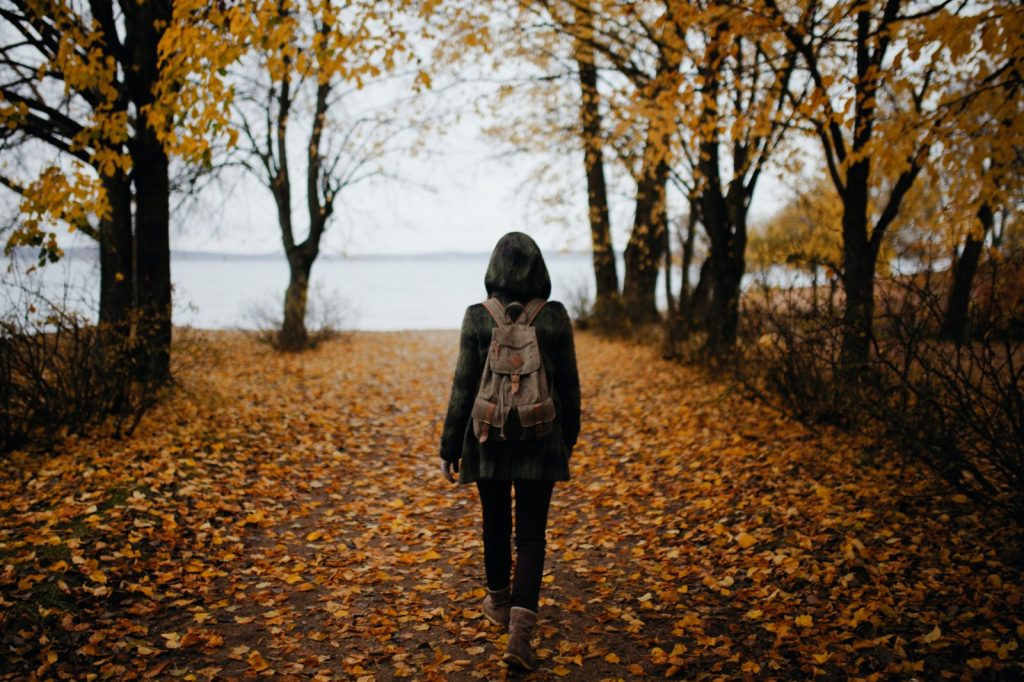 woman walking on pathway with falling leaves near body of water during daytime